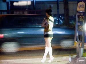 Una prostituta sul ciglio di una strada, le auto si muovo ad alta velocità.