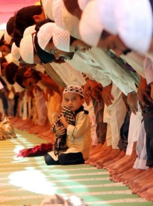 In India un bambino assiste alla preghiera.