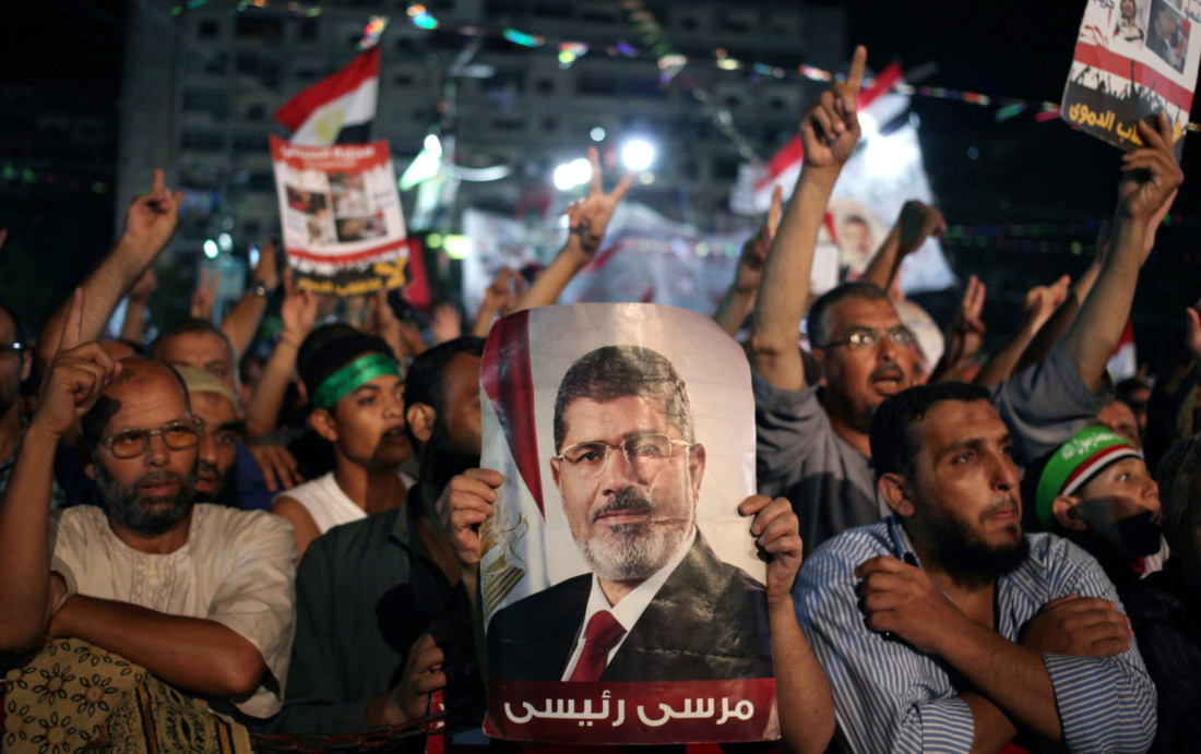 """Supporters of Egypt's ousted President Mohammed Morsi chant slogans one holding a picture of Morsi with Arabic writing that reads: """"Morsi is my president,"""" at Nasr City, where protesters have installed a camp and hold daily rallies, in Cairo, Egypt, Monday, July 29, 2013. Europe's top diplomat urged Egypt's government to reach out to the Muslim Brotherhood as she worked Monday to mediate an end to the country's increasingly bloody crisis, while the mainly Islamist protesters calling for the return of ousted leader Mohammed Morsi massed for more protests. (AP Photo/Khalil Hamra)"""